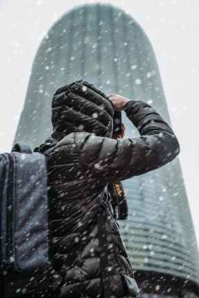 person wearing winter jacket while snowing